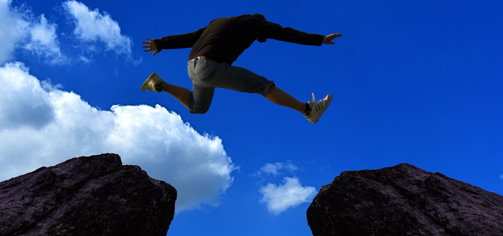 Runner leaping between two rocks against a blue sky