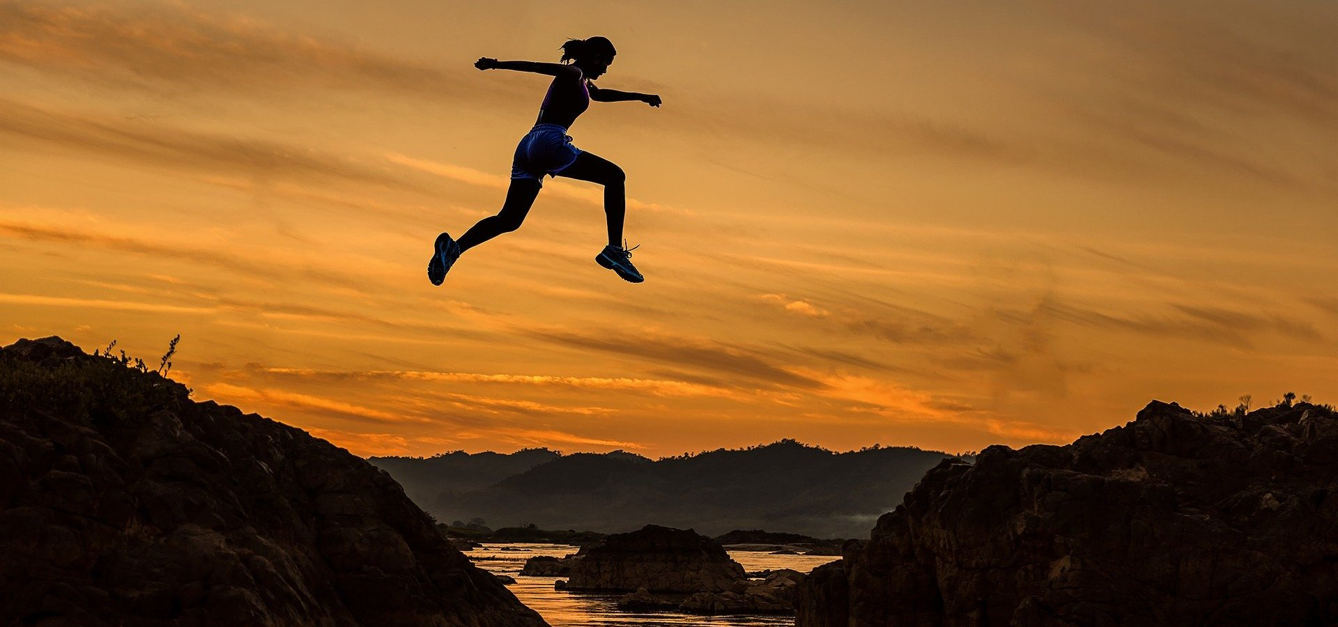 Woman running leaping between rocks at sunset.